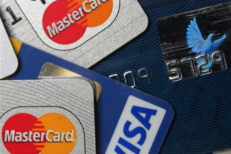 FILE - This file photo taken Nov. 18, 2009, a pile of MasterCard and VISA credit cards are displayed in Frankfurt, Germany. A sweater you buy for Christmas goes on sale for half price the next day. You might be able to get the difference back if you paid with a credit card.(AP Photo/Jochen Krause, File)
