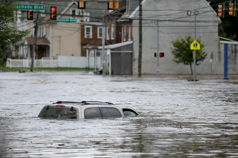 A vehicle sits in flood waters from Darby Creek on Springfield Road in Darby.
