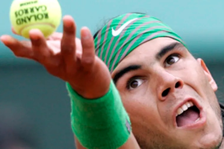 Rafael Nadal serves to Roger Federer en route to his lopsided victory. Nadal improved to 28-0 at Roland Garros.