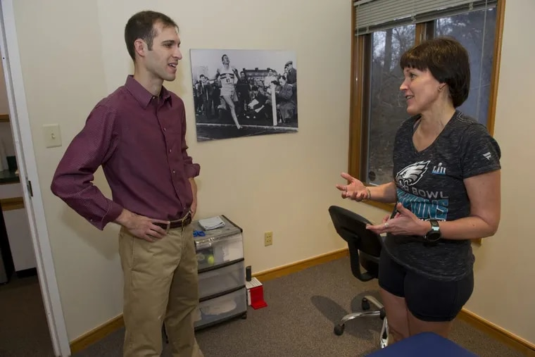 Flash Sports Physical Therapy and Performance Center physician Dr. J. Ryan Bair speaks with patient Marianne Bowman, 54, in his West Chester office on February 16, 2018. Flash is a cash-only physical therapy practice, so patients know up front what their cost will be and can bill their insurance later.