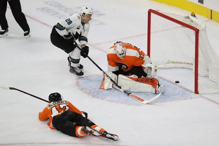 Timo Meier, center, of the Sharks scores between the legs of Brian Elliott, right, of the Flyers. Andrew MacDonald is at left.