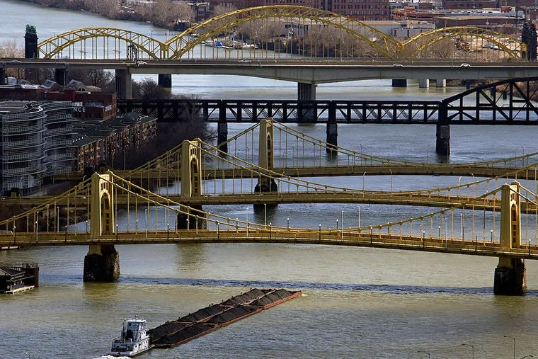 """A towboat and barges make their way up the Allegheny River under """"the Three Sisters,"""" three historic bridges named after (from foreground) Roberto Clemente, Andy Warhol, and Rachel Carson in downtown Pittsburgh. GENE J. PUSKAR / Associated Press"""
