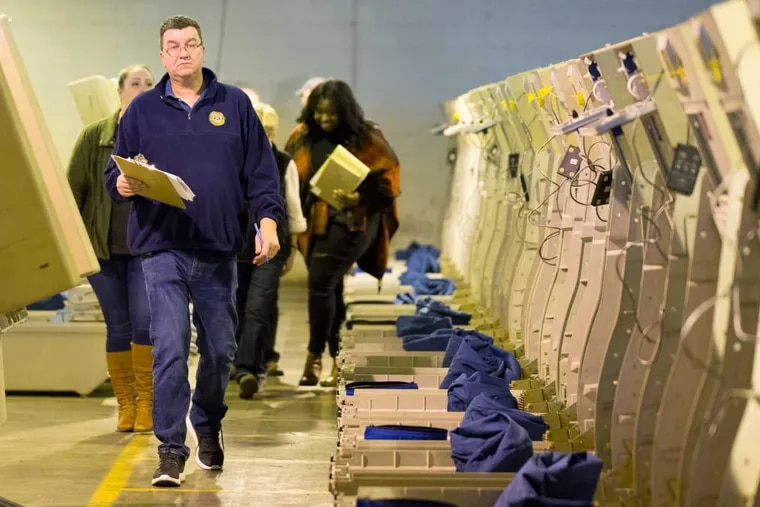 Civil service employee Joe Lynch, center, alongside voting machines in the Philadelphia City Commissioners' warehouse, works on an audit to recount the votes in 75 Philadelphia voting divisions, on Dec. 2, 2016.