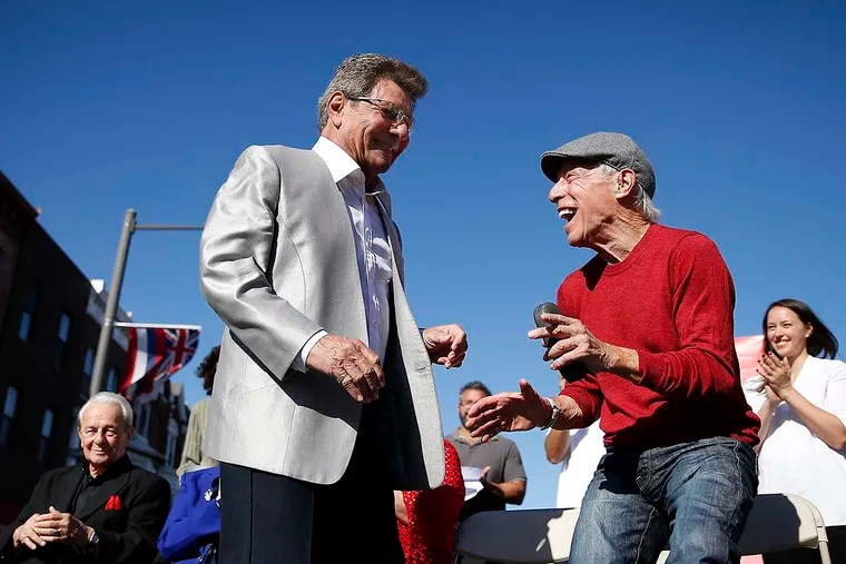 """Frankie Avalon, left, and Jerry Blavat, right, dance during the dedication of the mural """"South Philly Musicians Remix"""" in Philadelphia, PA on October 15, 2016."""