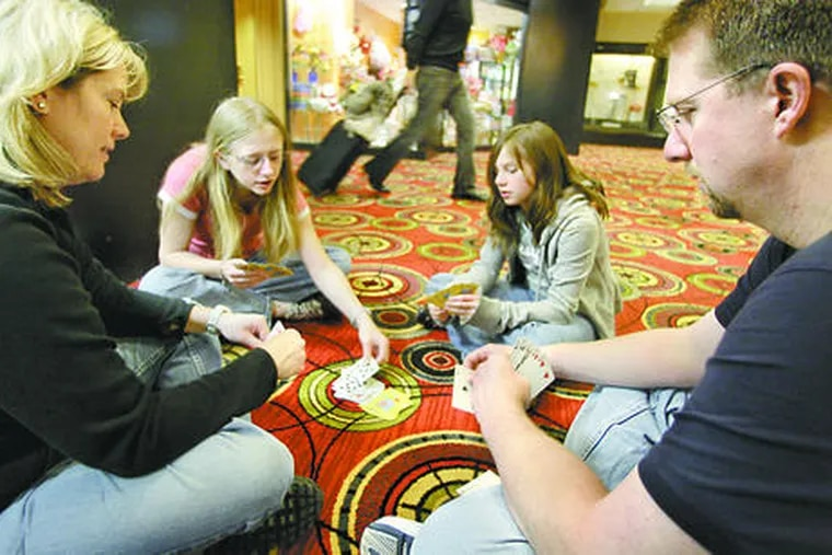 Tom and Kristina Waltz play cards with daughters Jessica (left) and Samantha at the O'Hare Hilton in Chicago, where flight delays and cancellations had trapped them since Tuesday.