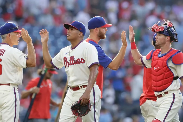Ranger Suarez, then a reliever, high fives Phillies Manager Joe Girardi as catcher Andrew Knapp high fives pitcher Zack Wheeler after the Phillies beat the Miami Marlins in Game 1 of a doubleheader on Friday, July 16, 2021 in Philadelphia.