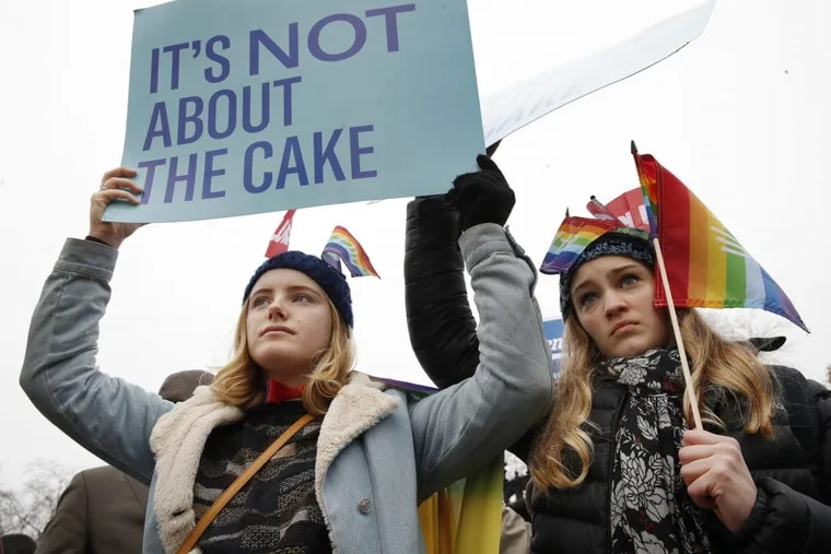 Lydia Macy, 17, left, and Mira Gottlieb, 16, both of Berkeley, Calif., rally outside of the Supreme Court, which on Tuesday heard the case of Masterpiece Cakeshop v. Colorado Civil Rights Commission.