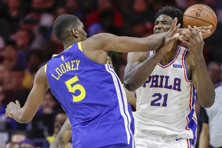 Sixers center Joel Embiid gets fouled by Golden State Warriors forward Kevon Looney during the third-quarter on Saturday.