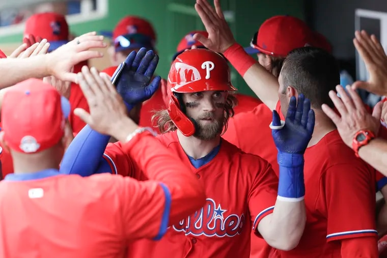Phillies right fielder Bryce Harper high-fives teammates after hitting a home run last week in spring training.