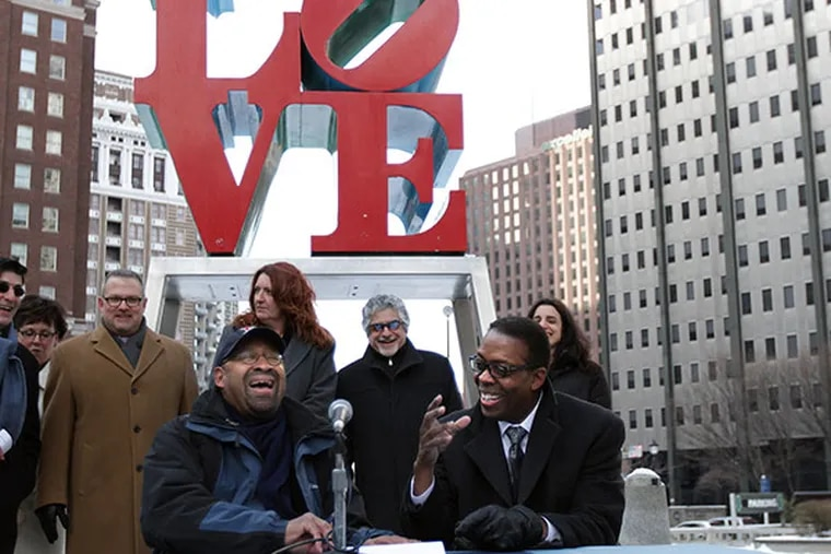 """Mayor Michael Nutter, left,  and Council President Darrell L. Clarke, right, reached an agreement that would allow the rehab of JFK Plaza and the sale of the garage beneath LOVE Park to move ahead. Mayor Nutter laughs as Clarke said it was his worst signature because it was so cold as the two signed a document that outlined their """"shared vision for LOVE Park"""" in Philadelphia, Pa. on February 9, 2014. ( DAVID MAIALETTI / Staff Photographer )"""