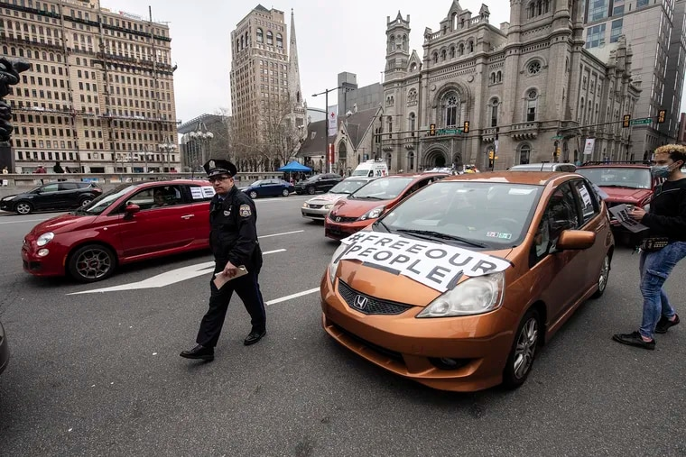 Police officers issue moving violation tickets to a caravan of drivers who blocked traffic in front of Philadelphia City Hall while protesting and demanding officials seek to remove people from jails, prisons, and detention centers in response to the COVID-19 outbreak.  Monday, March 30, 2020.