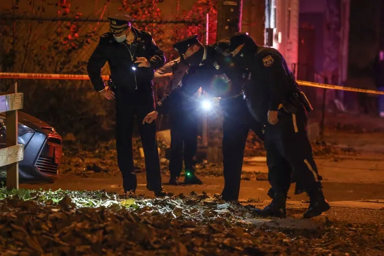 Police look over the crime scene at 31st and Arizona Streets in Strawberry Mansion on Tuesday night. A 44-year-old man was killed and a 45-year-old man was wounded. Police found 17 shell casings from two guns.