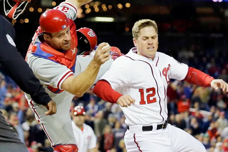 Philadelphia Phillies catcher Erik Kratz (31) hangs on to the ball to make the tag on Washington Nationals' Tyler Moore (12) for the out at home during the fourth inning of a baseball game at Nationals Park, Friday, May 24, 2013, in Washington. (AP Photo/Alex Brandon)
