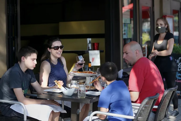 Melanie Santiago of Roxborough (second from left), her husband, Ricky (right), and their sons, Cole (left), 12, and Quinn (second from right), 9, eat pizza outside Jake's and Cooper's Wine Bar on Main Street in Philadelphia's Manayunk section on Friday, June 12, 2020. The city allowed outdoor dining to resume Friday for the first time since the city's coronavirus shutdown.