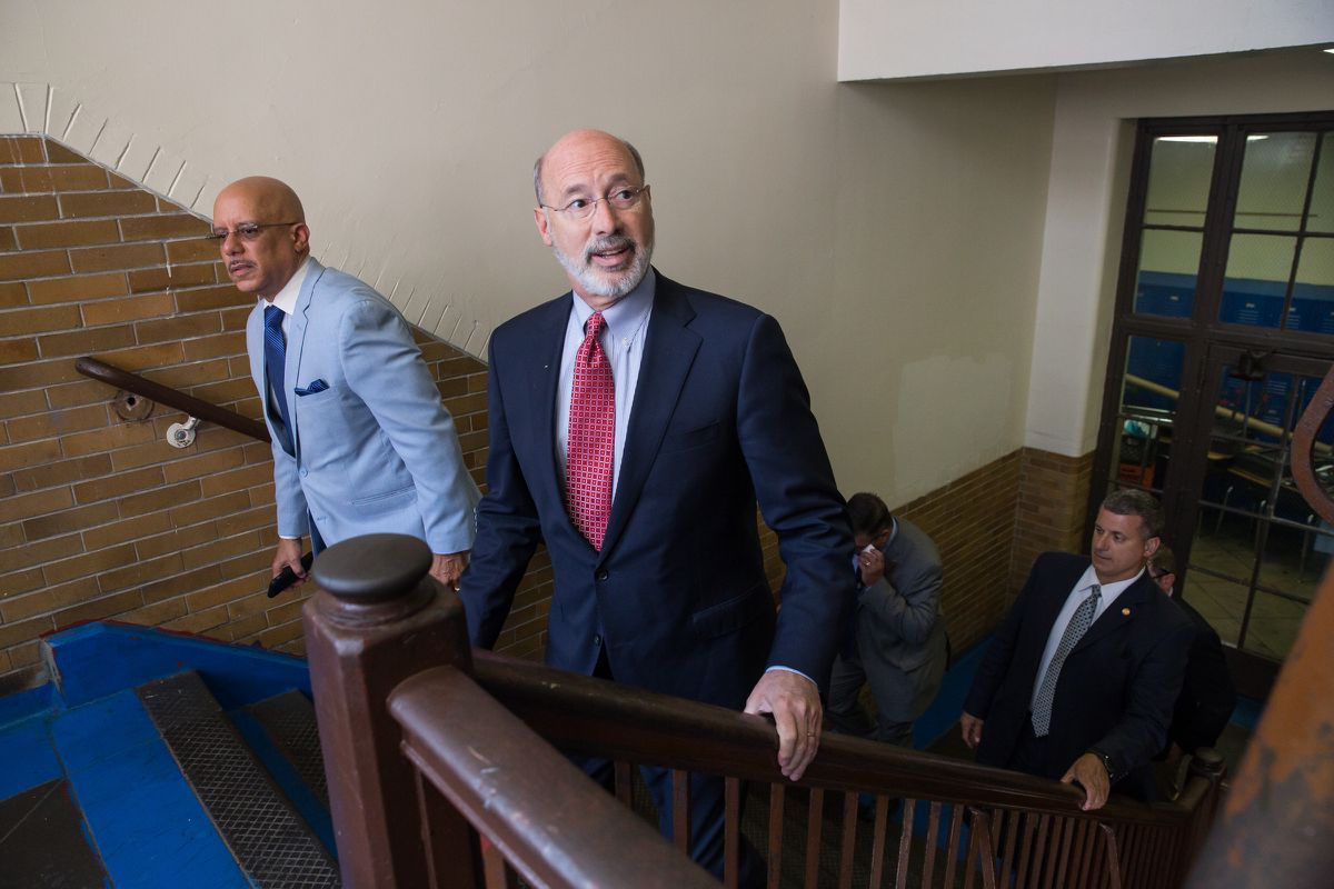 State Sen. Vincent Hughes (left) and Gov. Tom Wolf (center) arrive at Roosevelt School in Philadelphia, prior to a June 29 news conference to announce $7.6 million in state funding to repair damaged lead paint and plaster at 40 city schools.