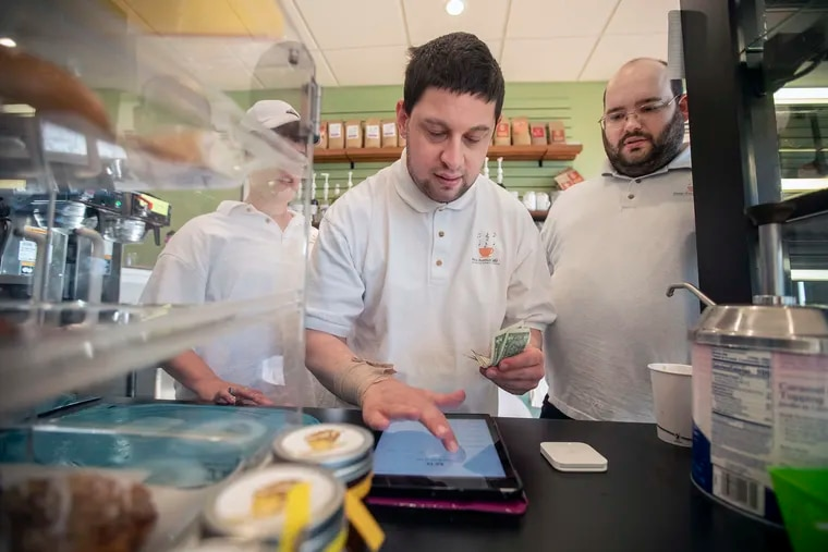 Eric Cohen, center, rings up a customer while manager Jonathan Dorfman, right, stands ready to help at the New Avenue Cafe in Havertown, PA on October 21, 2019.   The New Avenue Cafe operates inside the Kelly Center and employees special-needs adults.