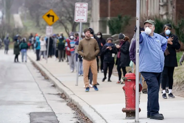 In this April 7 file photo, voters observe social distancing guidelines as they wait in line to cast ballots in the presidential primary election in Milwaukee.
