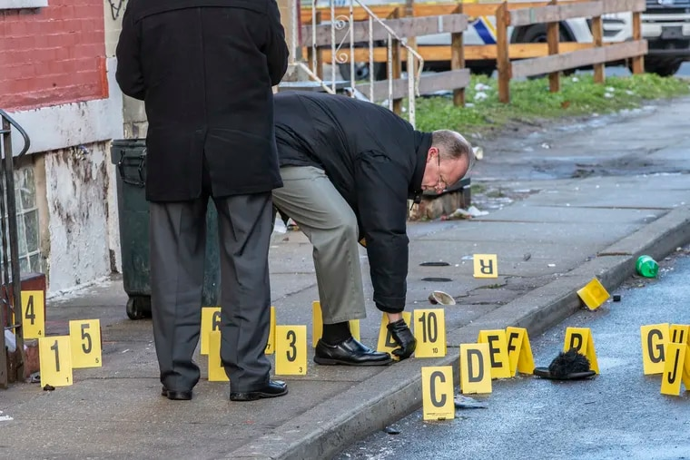 Philadelphia police investigators gather up the bullet shell casings on the 2400 block of North Patton Street Sunday morning, Jan. 19, 2020, after two men were found with gunshot wounds in the early hours of Sunday morning. Both men were taken to Temple University Hospital.