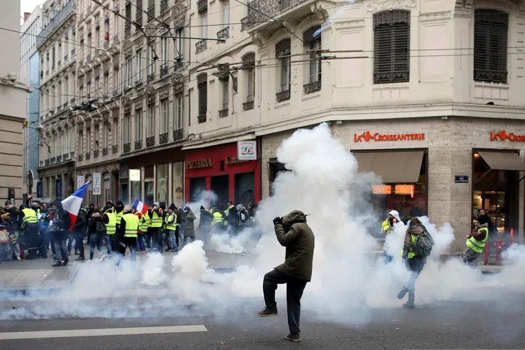 Demonstrators run away through tear gas in Lyon, central France, Saturday, Dec. 15, 2018. The demonstrations against France's high cost of living, sapped by cold weather, rain and recent concessions by French President Emmanuel Macron, were significantly smaller Saturday than at previous rallies. (AP Photo/Laurent Cipriani)