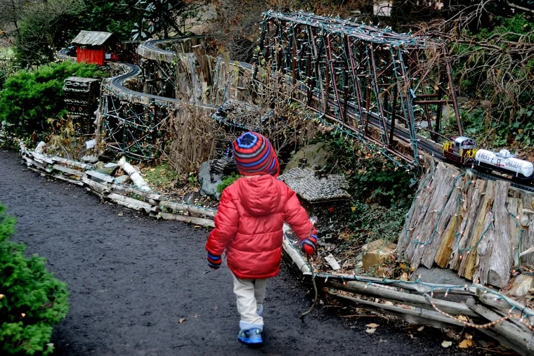 A youngster watches the popular Holiday Garden Railway made with logs and branches used to create unique tunnels and overhead trestles. at Morris Arboretum in December 4, 2014 file photo.