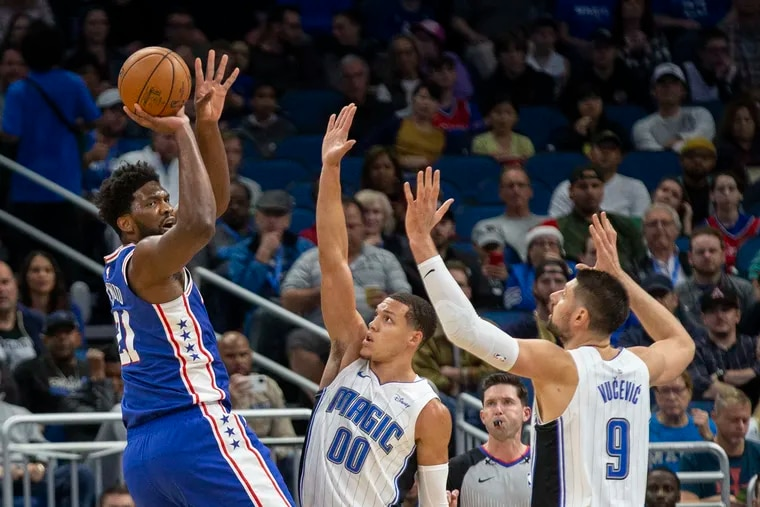 Center Joel Embiid (21) shoots over Orlando's Aaron Gordon (00) and Nikola Vucevic (9) during the first half of the Sixers' 98-97 loss Friday night.