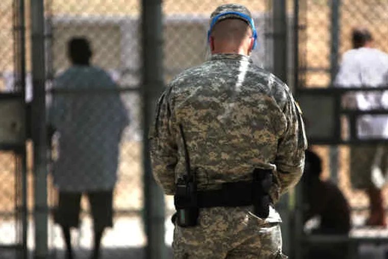 A guard watching over detainees Sunday in an exercise yard at Guantanamo Bay naval base. This photo, shot through a window, and the photo below were reviewed by the U.S. military.