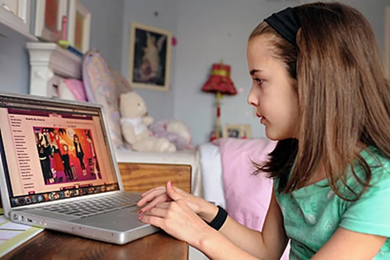 """Zero interest in dolls"""": Kelsey Mauger, 8, of North Wales, plays on her computer. She likes Club Penguin, where penguin avatars travel a virtual world and friends meet to chat online. (Sharon Gekoski-Kimmel / Staff)"""