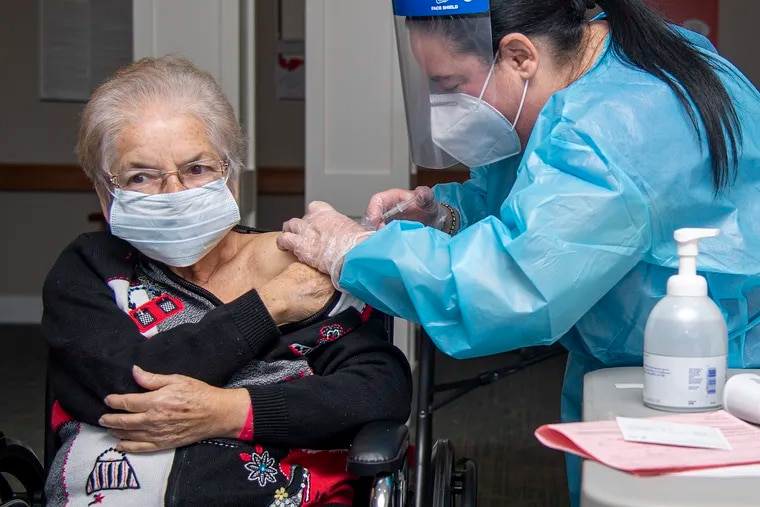 Nadine M. Mackey (right) injects the COVID-19 vaccine into nursing home resident Lydu Trudeau at Power Back Rehabilitation, in Phoenixville on Monday, Dec. 28.