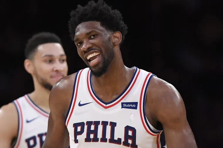 Sixers center Joel Embiid (right) smiles after scoring as guard Ben Simmons stands in the background.