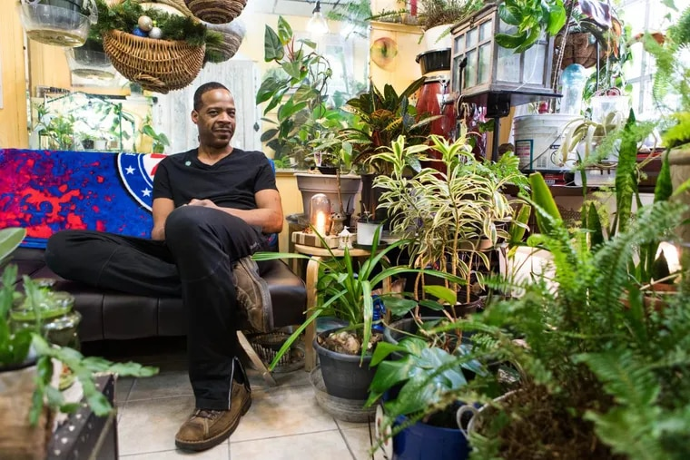 """Nakia Maples, also known as the """"Philly Plant Guy,"""" sits among his plants in the plant room of his South Philadelphia home."""