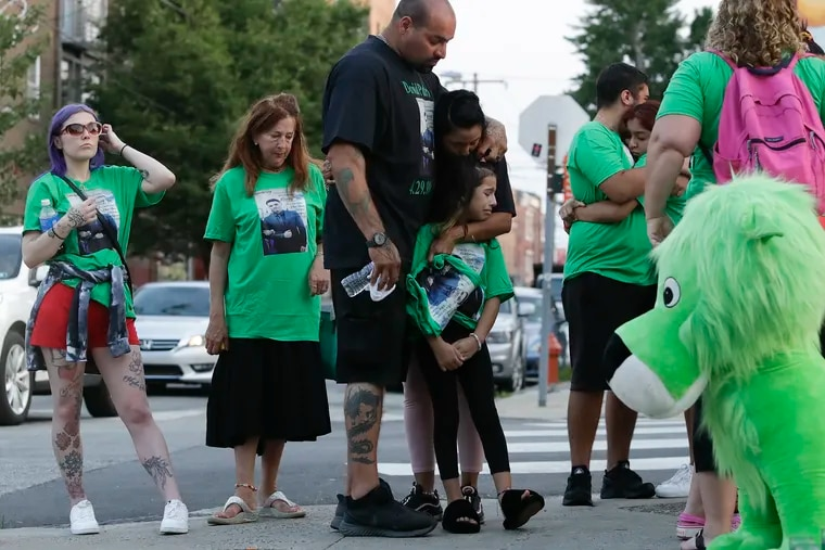 David Padro, in black shirt, embraces family during a vigil Sunday for his son David Padro Jr., who was killed outside Pat's Steaks in South Philadelphia.  Friends and family gathered for a vigil there.  A Reading man is charged with murder.