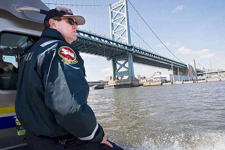 Marine Unit Officer Joseph Curley passes under the Ben Franklin Bridge during a routine patrol along the Delaware River. (Alejandro A. Alvarez/Staff)