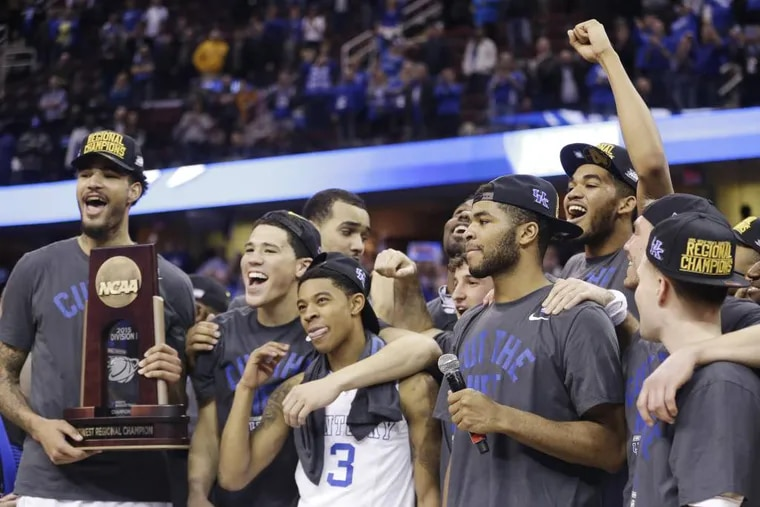 Kentucky players celebrate with the regional championship trophy after a 68-66 win over Notre Dame in a college basketball game in the NCAA men's tournament regional finals, Saturday, March 28, 2015, in Cleveland. (AP Photo/Tony Dejak)