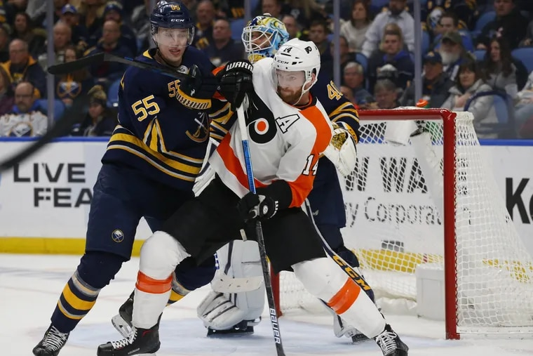 Buffalo Sabres defenseman Rasmus Ristolainen (55) and Flyers forward Sean Couturier  battle in front of the net.