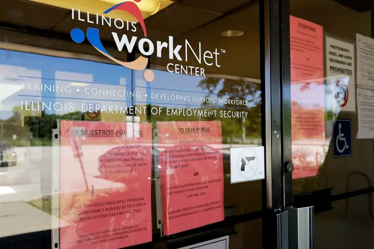 In this June 11 photo, information signs are displayed at the closed Illinois Department of Employment Security WorkNet center in Arlington Heights, Ill.