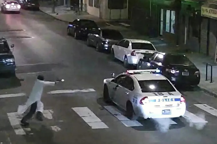 In this Jan. 7, 2016, image made from a video provided by the Philadelphia Police Department, a gunman runs toward a police car driven by Philadelphia Police Officer Jesse Hartnett in Philadelphia.