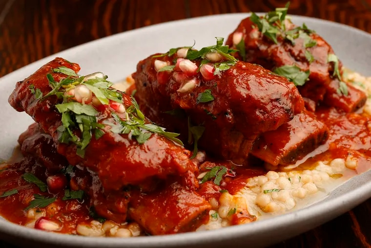 Braised veal short ribs served with herbed Israeli couscous and pomegranate seeds from Charley Dove at 20th and Spruce Streets.