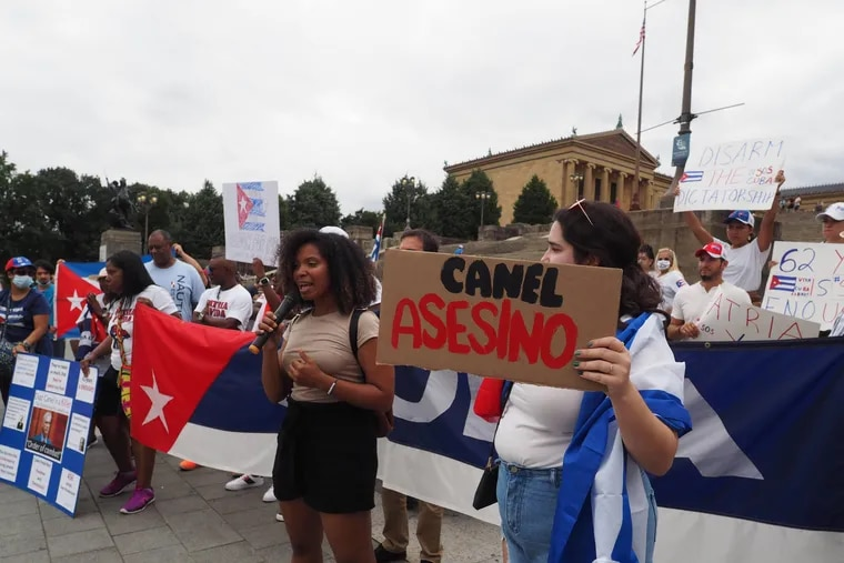 """Cubans in Philadelphia, supporting the protests on the island against the Cuban regime, on the steps of the Art Museum July 18. Holding a sign is one of the organizers, Amalia Daché, an Afro-Cuban American scholar and an associate professor at the University of Pennsylvania. The sign next to Daché says """"Canel Murderer,"""" referring to Miguel Díaz-Canel, president of Cuba. This was the biggest protest organized by this community in recent Philadelphia history with around 200 protesters."""