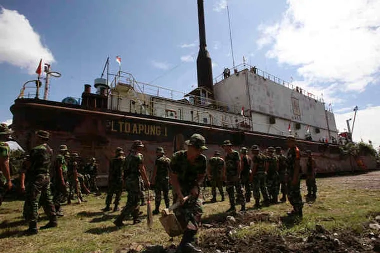 Indonesian soldiers earlier this month cleaning the area near an electricity-generator ship that was swept ashore by the 2004 tsunami in Banda Aceh, which has few other visible reminders of the tsunami today.