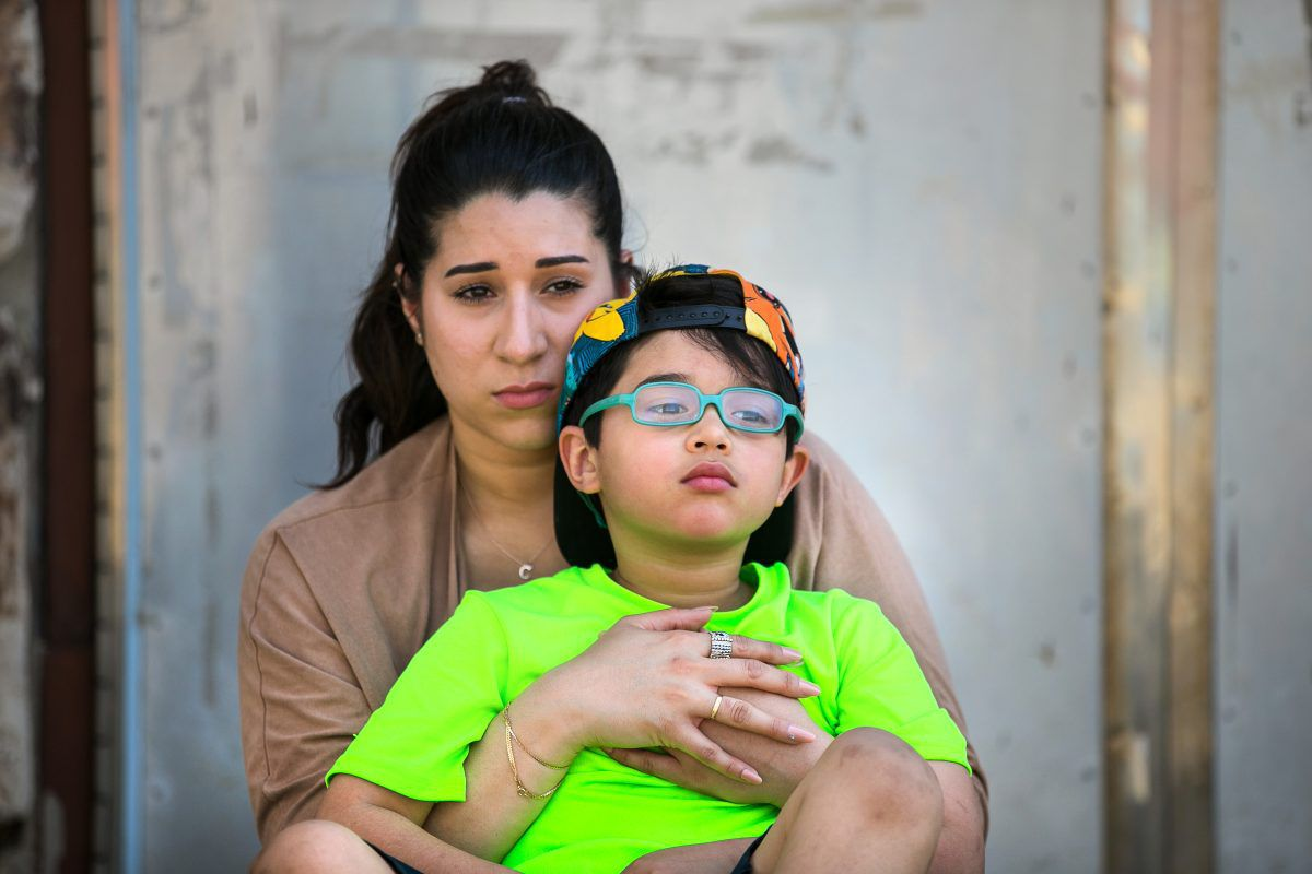 Cristine Gonzalez, back, holds her six-year-old son Dean Pagan, front, at a playground in Philadelphia. Dean was severely lead poisoned at Comly Elementary School.