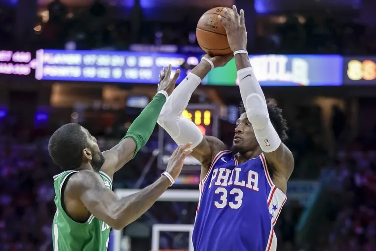 Sixers forward Robert Covington shoots over Boston Celtics guard Kyrie Irving during the game between the teams at the Wells Fargo Center in October.