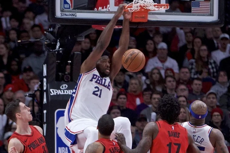 Sixers center Joel Embiid, center, dunks over several Trail Blazers, in the Sixers' loss to the Blazers Thursday night.