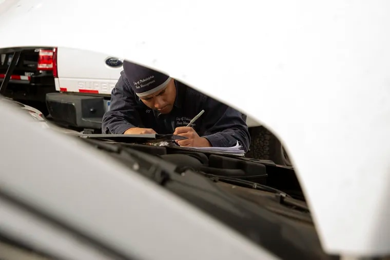 """Otoniel """"O.T."""" Figueroa inspects a car at South Philly garage he calls home. Figueroa, 39, started working for the city as a mechanic when he was in high school as part of what's become the city's longest running and most successful apprenticeship program."""