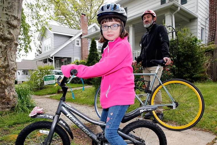 Willa Bonaparte and her father, Joe, in their Collingswood neighborhood. Collingswood is not the only local town to limit cycling to elementary school. Haddon Township has a ban as well.