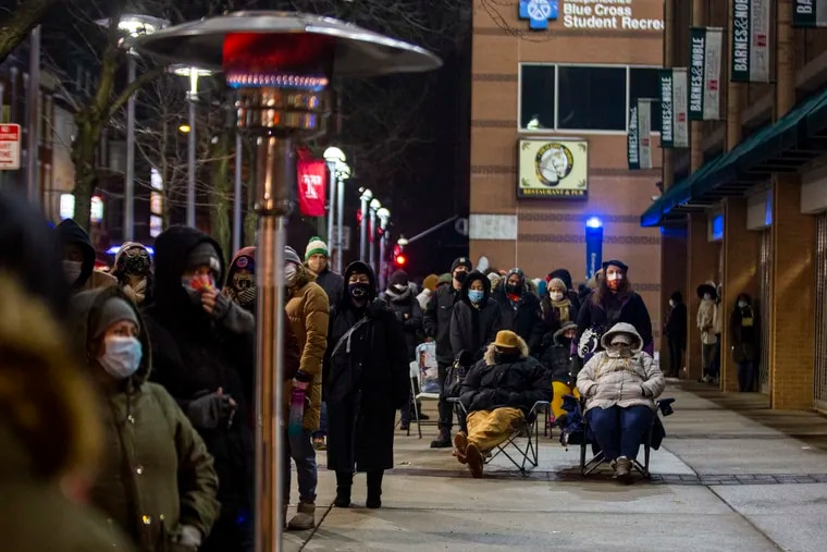 """David Burke (seated, left) and his wife, Stephanie Burke, sat in line Friday night, just before midnight, as they approached their seventh hour waiting to receive the COVID-19 vaccine at the Liacouras Center. """"Right now there is no real way to get it unless you wait out and stay out in these lines,"""" David Burke said. """"It was the perfect opportunity. It's good it ain't raining or snowing."""""""