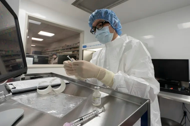 A pharmacist labels syringes in a clean room where doses of COVID-19 vaccines will be handled at Mount Sinai Queens hospital in New York.