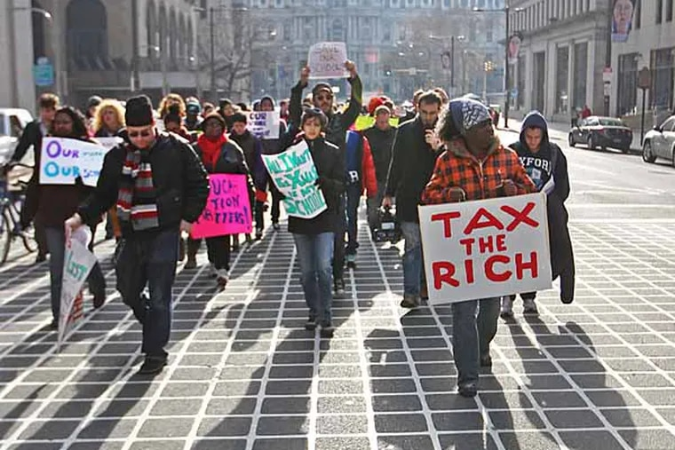 Marchers protesting the 37 school closings by the Philadelphia School District cast long shadows down Broad Street as they marched from around City Hall to 440 N. Broad Street, the district's headquarters. ( MICHAEL BRYANT / Staff Photographer )