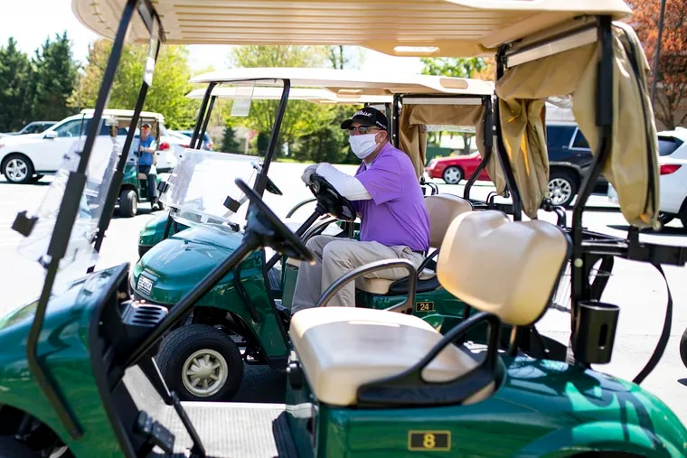 Shawn Quinn, 52, the director of outside operations for the Merchantville Country Club, sterilizes carts and helps get members equipment on Saturday. New Jersey and Pennsylvania have allowed golf courses to reopen this weekend with coronavirus-inspired restrictions.