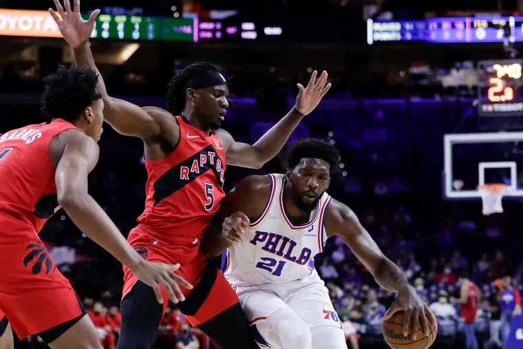 Sixers center Joel Embiid dribbles the basketball against Toronto Raptors forward Precious Achiuwa during the first quarter of Thursday's preseason game.