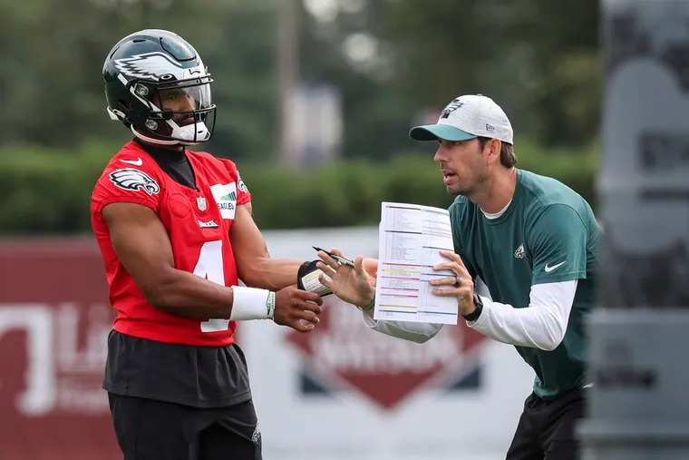 Eagles quarterback Jalen Hurts talks with offensive coordinator Shane Steichen during practice Tuesday at the NovaCare Complex.